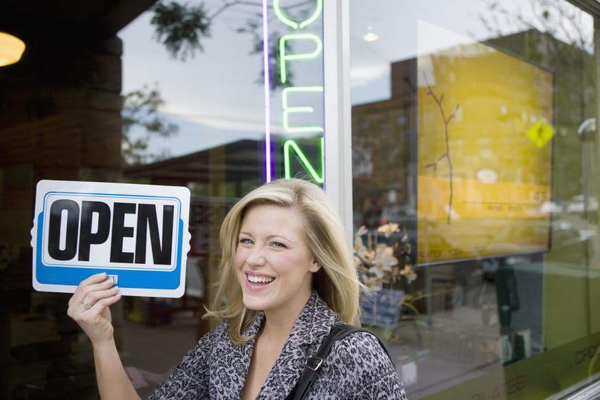 "Woman holding ""Open"" sign in front of her business"
