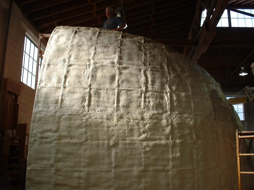 Wooden frame surrounded by closed-cell spray foam