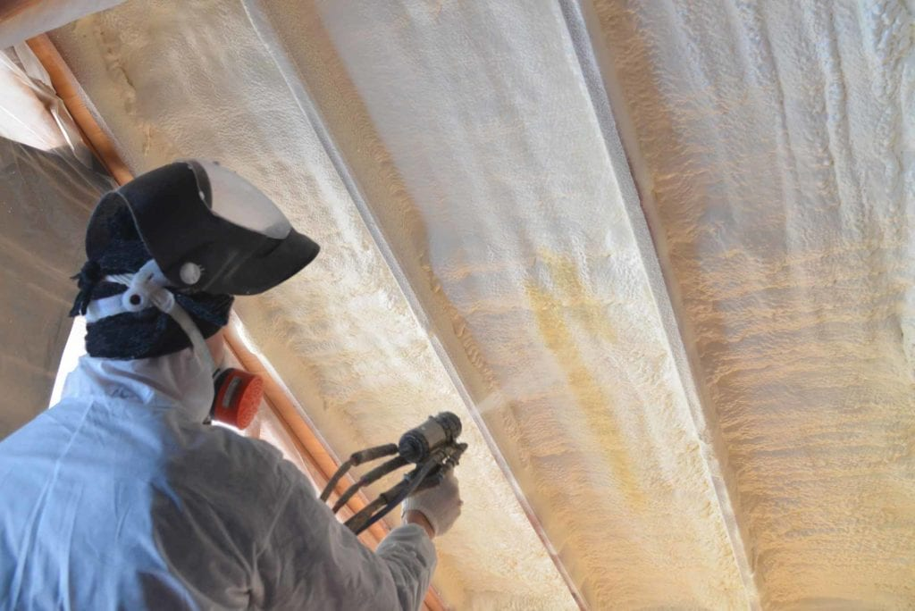 Worker spraying foam insulation in attic